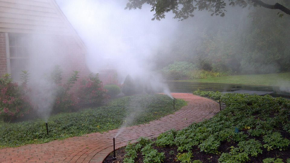 This is mist coming from an irrigation system along a brick path.