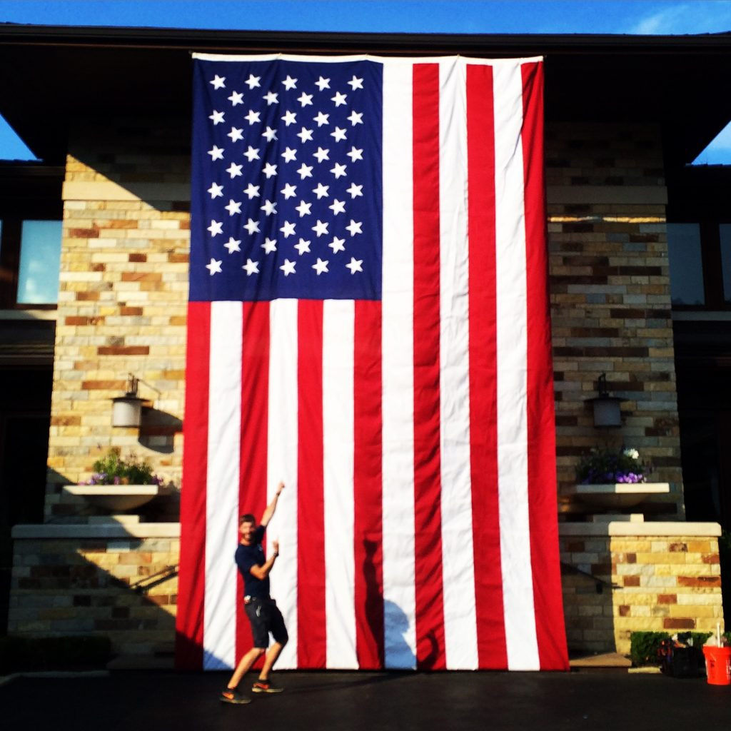 This is a man pointing at a large American flag hanging from the side of a house.