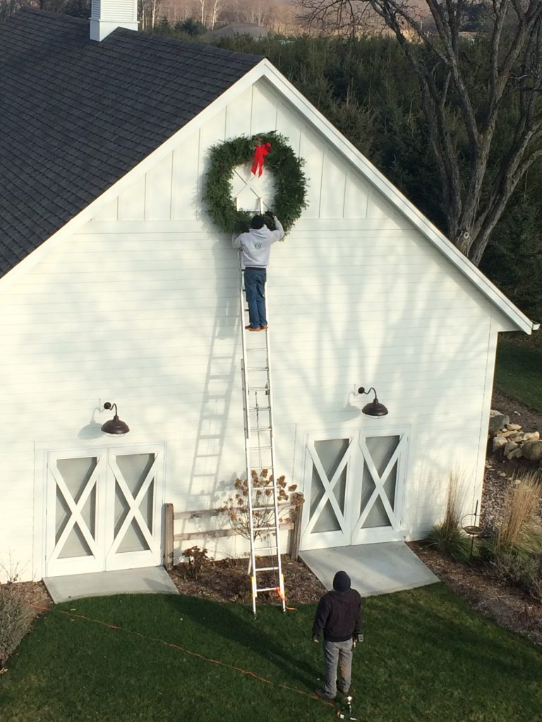 These are two men hanging a wreath on the side of a house.